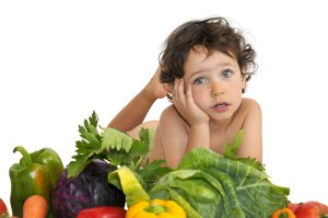 Foto de un niño rodeado de verduras