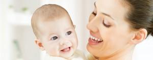 Foto de una mamá cogiendo a su bebé sonriendo